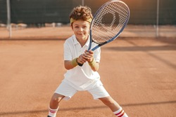 Positive active school aged boy with racket looking at camera while playing tennis on court