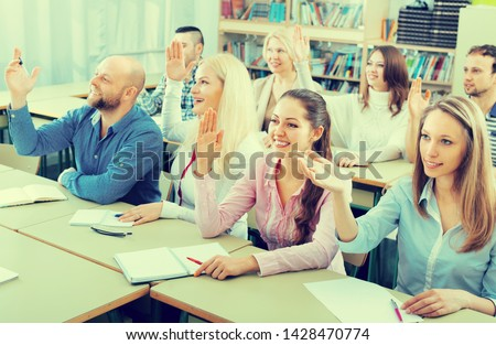 Positive adult students sitting in classroom with hands up. Focus on girl