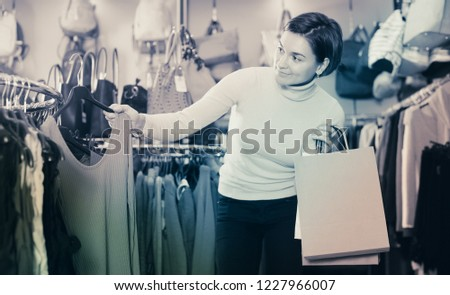 Positive adult woman choosing colorful blouse in women's cloths shop