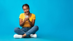 Positive African American Girl Using Smartphone Browsing Internet Sitting Over Blue Studio Background. Mobile App. Panorama, Empty Space