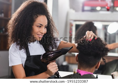 Positive african american hairdresser holding hair dryer near client on blurred foreground Stock photo ©