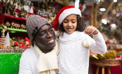 Positive african american man with small daughter in hats buying decoration at Christmas fair outdoor