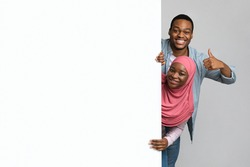 Positive african american muslim couple posing with big empty board over grey studio background. Smiling young black man and woman in hijab standing next to blank advertising placard, showing thumb up
