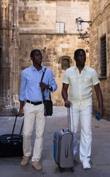 Positive african american travelers strolling with luggage along city street on summer day.