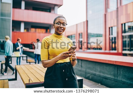 Positive african american woman in casual wear and spectacles looking at camera and holding mobile phone, portrait of attractive dark skinned hipster guy  using smartphone and 4G internet for chatting