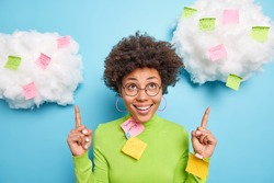 Positive African American woman smiles toothily and points above being in good mood surrounded with colorful sticky notes makes list to do for week wears spectacles green turtleneck isolated on blue