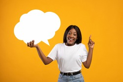 Positive african american young lady holding empty communication bubble and pointing finger up, yellow studio background. Black lady in casual with blank clipart, sharing creative ideas