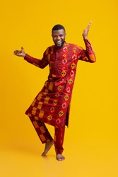Positive african man in traditional dress dancing over yellow studio background