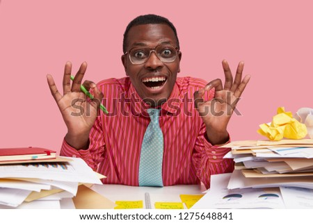 Positive Afro American man makes ok gesture with both hands, smiles broadly, demonstrates everything is alright, dressed in formal clothes, holds pen, does paper work, isolated over pink background