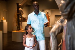 Positive Afro father and daughter looking at exhibits of medieval sculpture on exposition of museum