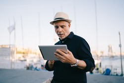 Positive aged male in casual outfit surprised at information from tablet screen while sitting against sea port with boats and yachts