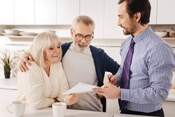 Positive aging couple owners meeting financial adviser at home