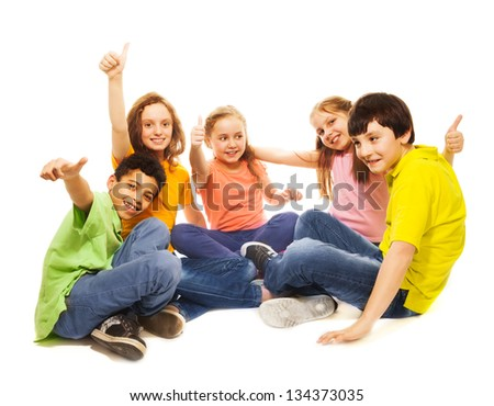 Positive and happy kids sitting with thumb up gesture together, smiling, laughing