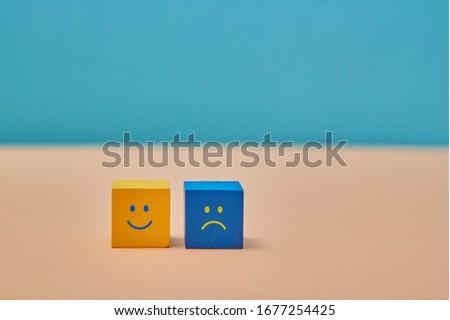 Positive and negative thinking, attitude. Positivity, negativity. Duality principle. Smile, sad emoji on wooden cubes