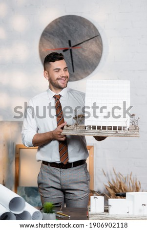 positive architect holding building maquette while standing at workplace Photo stock ©