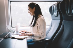 Positive asian businesswoman working during railroad trip reading news and checking mail on laptop computer, smiling prosperous female blogger share content and communicating online in wagon of train