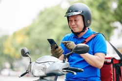 Positive Asian delivery man accepting another order via mobile application on smartphone