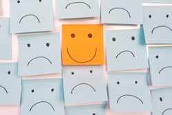 Positive Attitude and Happy Concept. Hand Drawn A Smile Face And Sad Emotion on Sticky Note Background.