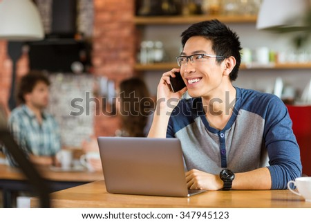 Positive attractive asian man in glasses using laptop and talking on cellphone in cafe #347945123