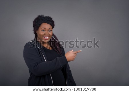 Positive attractive young African American woman, points aside with finger and having cheerful expression, shows something at blank space, isolated over gray wall. Advertisement and ethnicity. #1301319988