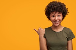 Positive attractive young female with Afro hairstyle, points aside with cheerful expression, shows something amazing at blank space, isolated over bright yellow backgroud. Advertisement and ethnicity
