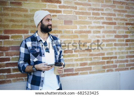 Positive bearded guy dressed in trendy casual outfit enjoying free time outdoors standing on wall promotional background, handsome male hispanic model texting messages on smartphone holding coffee cup #682523425
