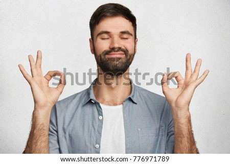 Positive bearded male model wears denim shirt, makes ok gesture and closes eyes, has happy expression, isolated over white background. Optimistic male expresses his approval. Body language concept