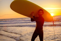 Positive bearded man in wetsuit carrying surfboard over head against waving sea and sunset sky on resort
