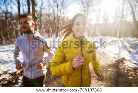 Positive beautiful young healthy couple running with sportswear through the forest in the sunny winter morning.
