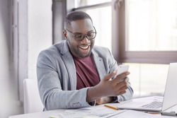 Positive black African American businessman downloads file on smart phone, sits in front of opened laptop, involved in distance job, being at his cabinet. Dark skinned male makes transfer online