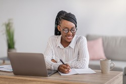 Positive black business woman with stylish glasses manager working from home during COVID-19 pandemic, using modern laptop and taking notes, sitting at workdesk in living room, copy space