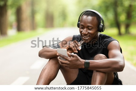 Positive black sportsman eating protein bar and using phone while resting, exercising at park, empty space