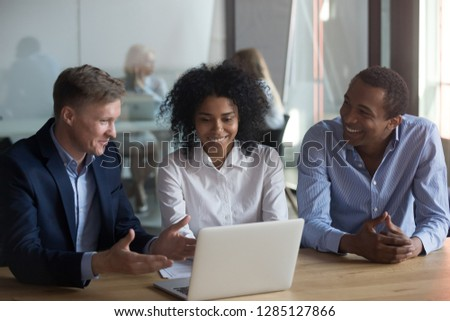 Positive black woman sitting at desk with diverse male colleagues working together in coworking area using laptop corporate program create a new project share fresh ideas having common business goal
