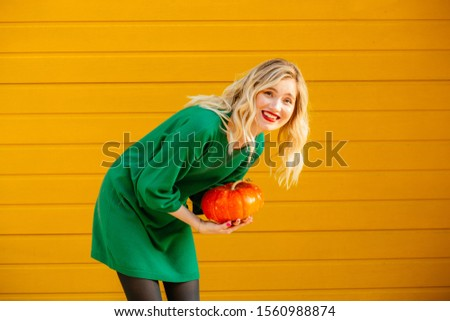 Positive blond glamour female with red lips and make up laughing holding orange pumpkin on yellow background outdoor portrait. Healthy food zero waste concept. #1560988874