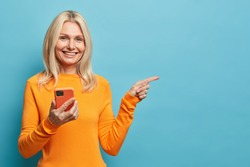 Positive blonde woman has happy smile holds mobile phone points away on copy space uses modern technologies being always in touch isolated on blue background. Middle aged lady with cellular.