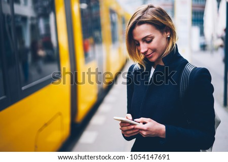 Positive blonde woman holding cellular updating information about city transport on web page, smiling hipster girl satisfied with online ticket service paying for electric transport via smartphone