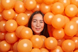 Positive brunette Asian woman surrounded by orange inflated air balloons prepares birthday surprise for friend smiles gladfully at camera has festive mood. People holiday decoration concept.