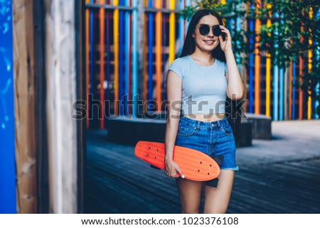 Positive brunette hipster girl in black sunglasses standing on street and holding orrange skateboard for riding outdoors.Cheerful young woman in spectacles standing against colorful background