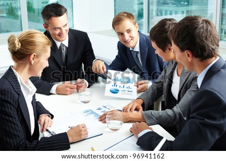 Positive business people holding a meeting to sum up the results of the year
