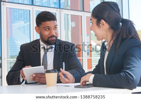 Positive business people working and using tablet at table. Business man and woman wearing formal clothes and sitting with building glass wall in background. Business issues concept.