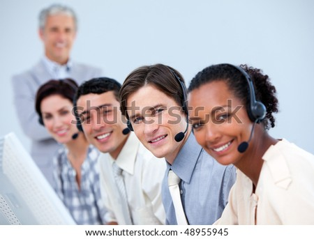 Positive business people working with their manager in a call center