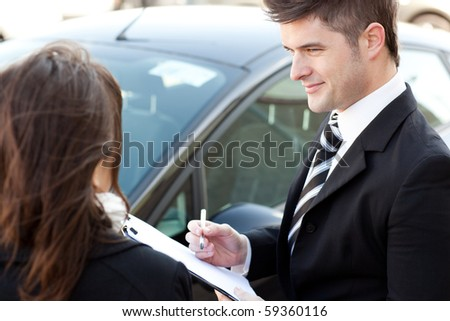 Positive businessman undersign a car contract outdoors