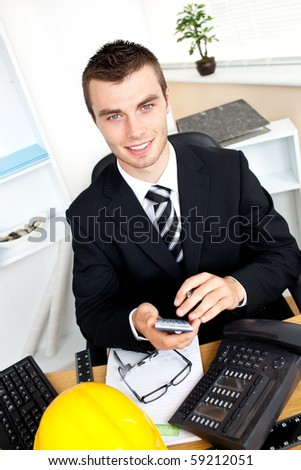 Positive businessman using his calculator looking at the camera in his office