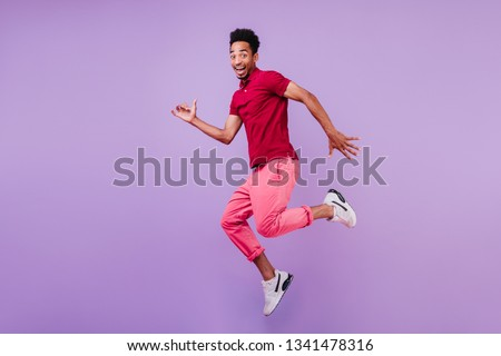 Positive carefree african man in sport shoes dancing on purple background. Handsome glad guy in pink pants jumping with smile. #1341478316