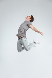 Positive carefree casual young man jumping in the air isolated on a white background.