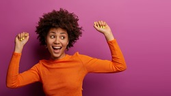 Positive carefree young woman with Afro hairstyle feels relaxed and happy, has fun at party, gazes aside, has beaming smile, isolated on purple background. People, hapiness, lifestyle concept