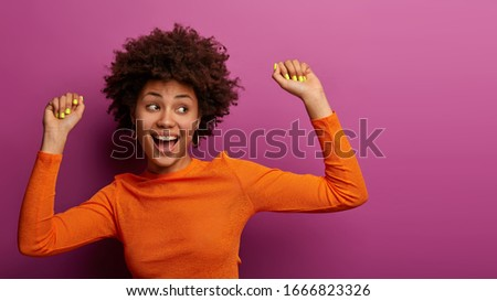 Positive carefree young woman with Afro hairstyle feels relaxed and happy, has fun at party, gazes aside, has beaming smile, isolated on purple background. People, hapiness, lifestyle concept Foto stock ©
