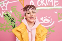 Positive carefree youngster with curly hair smiles gladfully wears braces on teeth has fun in public place wears hoodie and yellow vest poses against grunge graffiti wall. Happy fashionable teenager