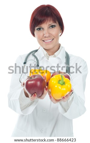 Positive caucasian female doctor holding fresh fruits and vegetables, over a white background