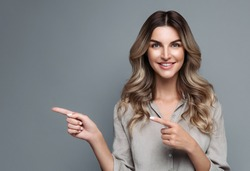 Positive caucasian female promoter with curly hair, points away with both fore fingers, shows blank copy space for your advertising, offering, product, promotion text,  isolated over grey background.